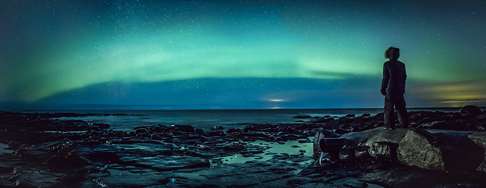 Teenage boy watching Northern Lights from rock, Reykjanesbaer, Iceland - 1177-2140