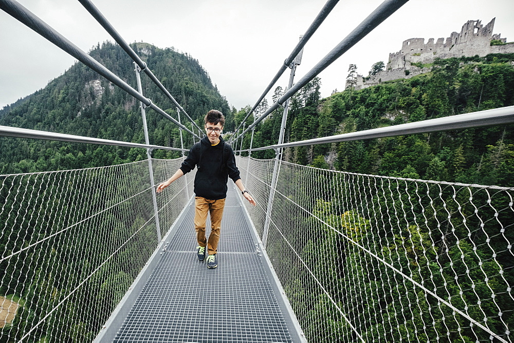 Teenage boy walking across Highline 179 suspension bridge, Tyrol, Austria