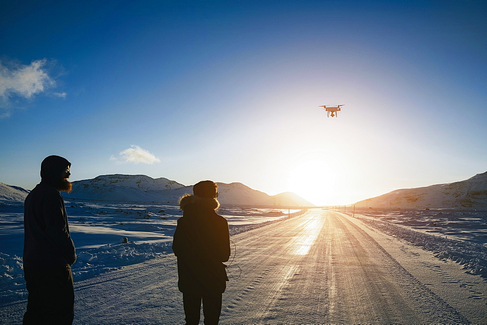 Father and son flying drone over remote, snow covered road, Reykjadalur, Iceland