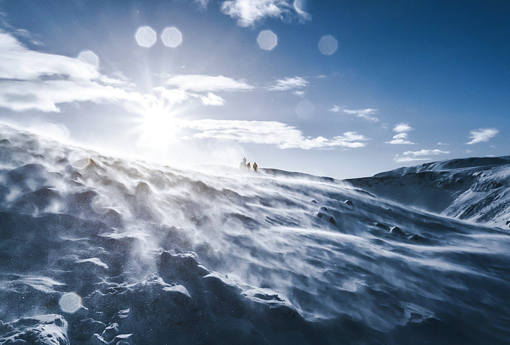 People walking along sunny, windy, snow covered mountain, Reykjadalur, Iceland