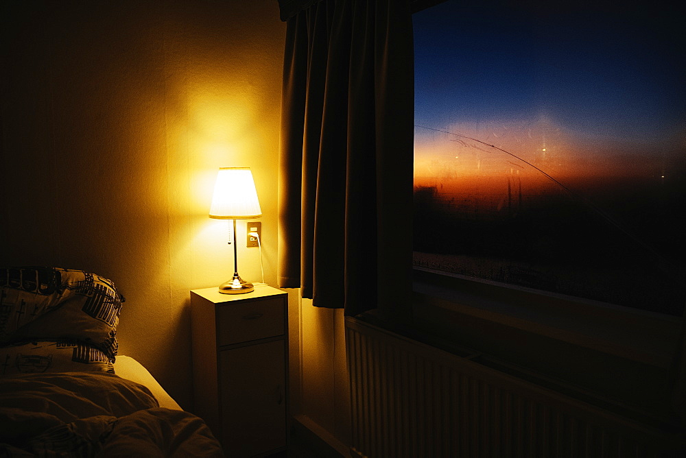 Bedside lamp illuminating bedroom corner next to window with view of dusk sky