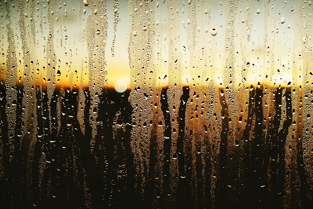 Raindrops and condensation on window with scenic sunset view