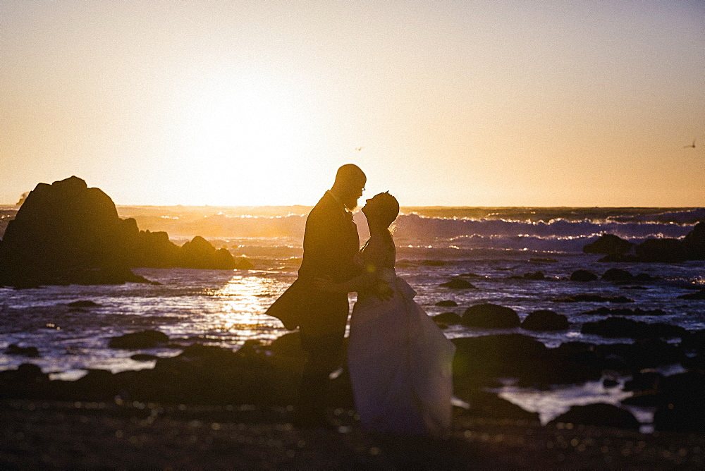 Silhouette bride and groom on tranquil sunset ocean beach, Monterey, Lucas Point, California, USA