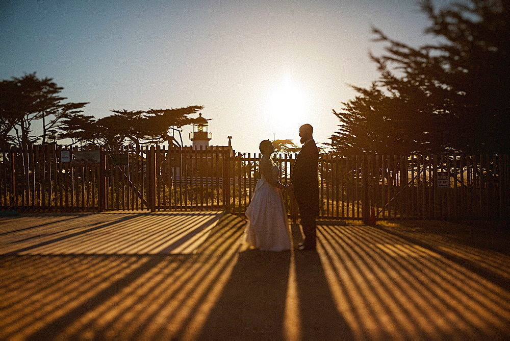 Bride and groom standing outside sunny lighthouse, Monterey, Lucas Point, California, USA