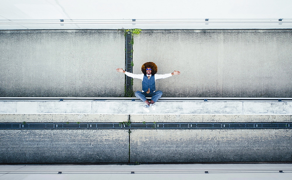 View from above portrait exuberant young man on urban ledge