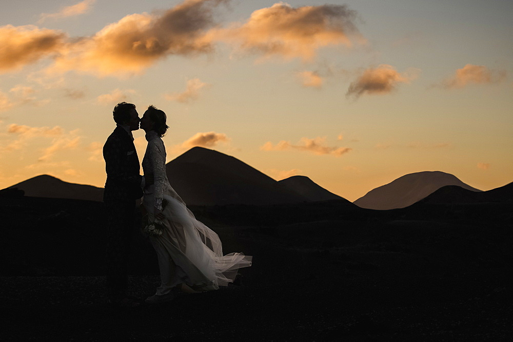 Silhouette bride and groom kissing at dusk with tranquil mountains in background