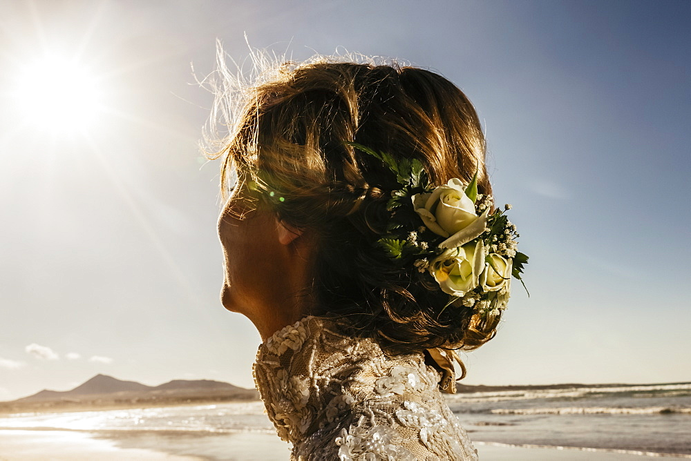 Bride with flowers in hair on sunny ocean beach