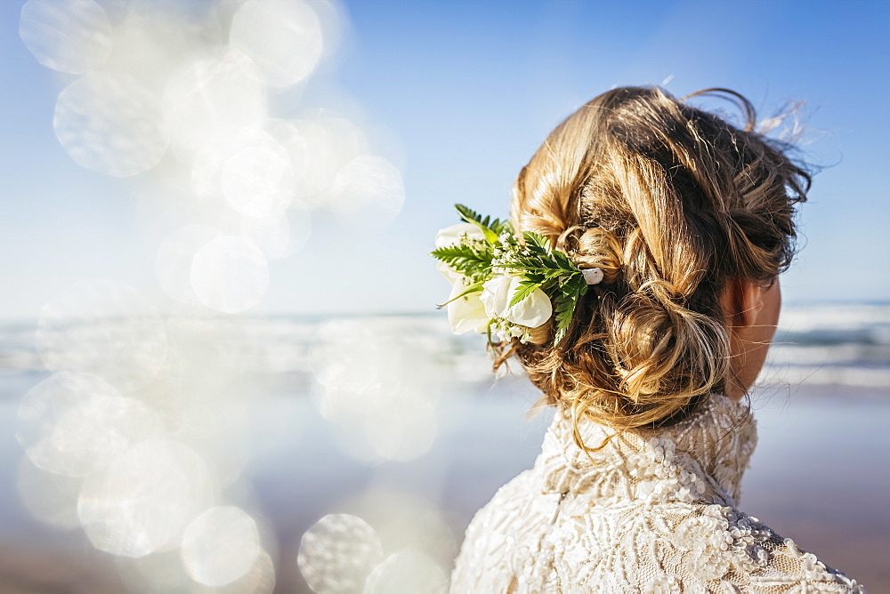 Blonde bride with flowers in hair on sunny beach