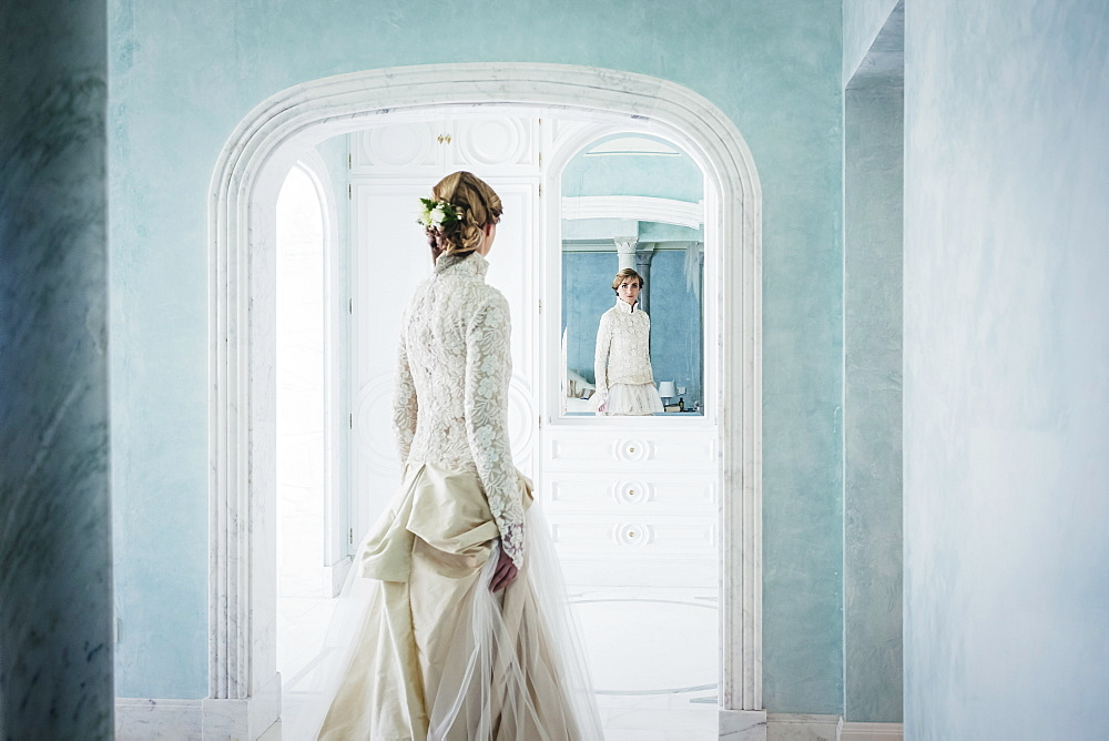Elegant bride in lace wedding dress at mirror