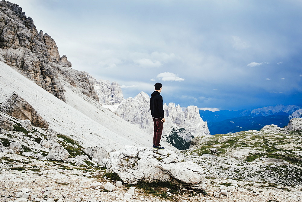 Teenage boy standing on rock overlooking rugged mountains, Drei Zinnen Nature Park, South Tyrol