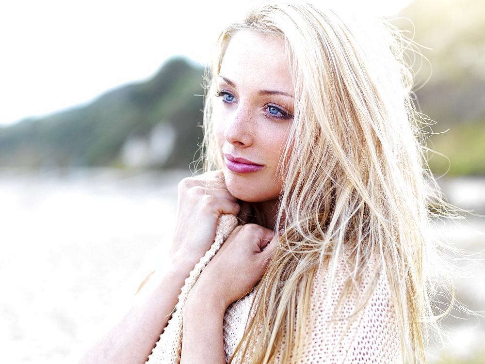 A teenage girl looking serenely away while standing on a beach
