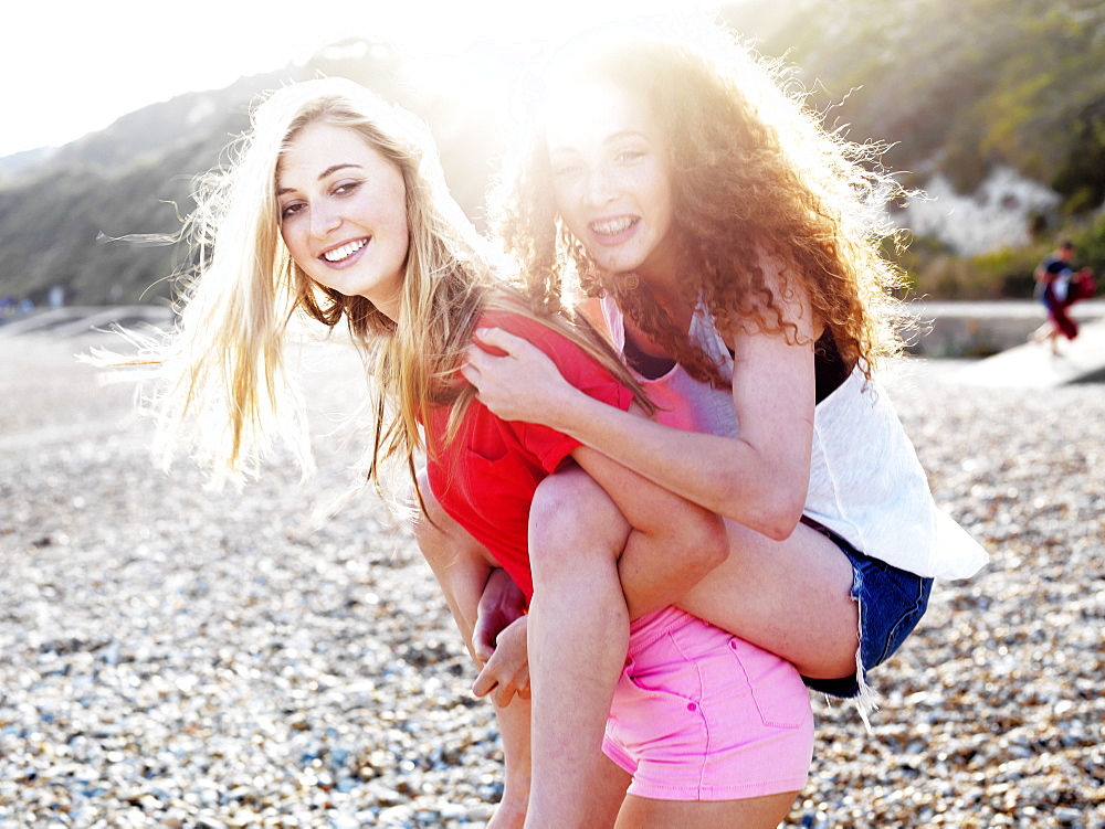 A young woman giving her teenage friend a piggyback ride at the beach