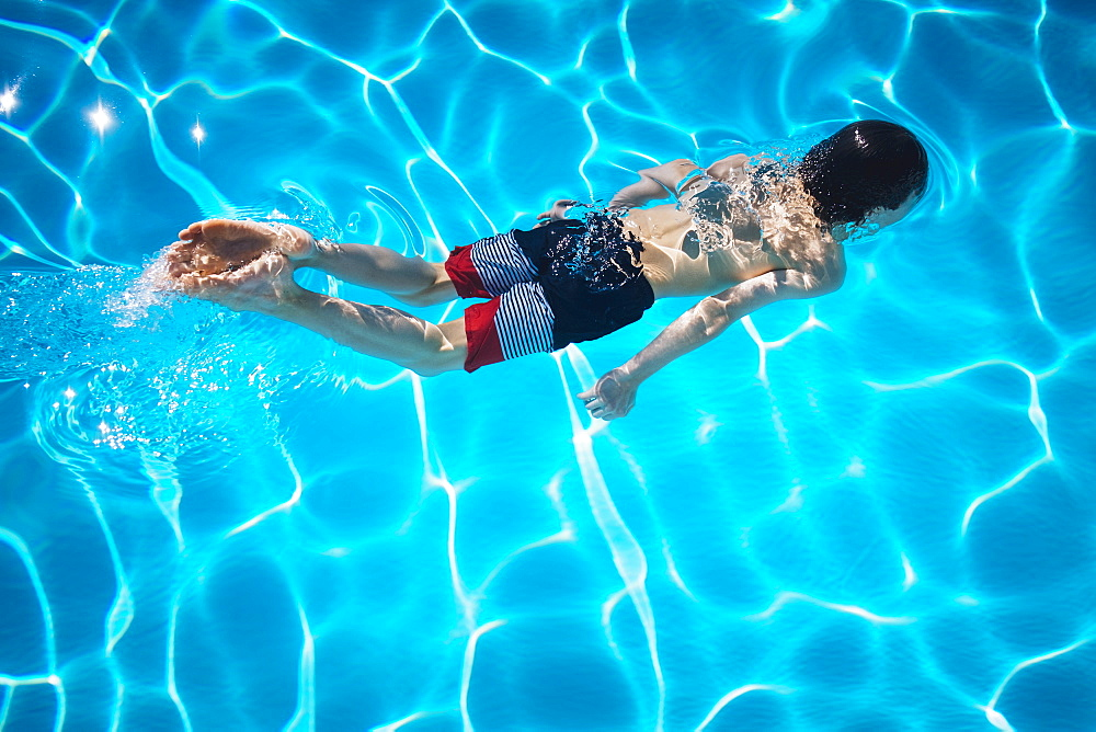 Boy swimming in blue swimming pool