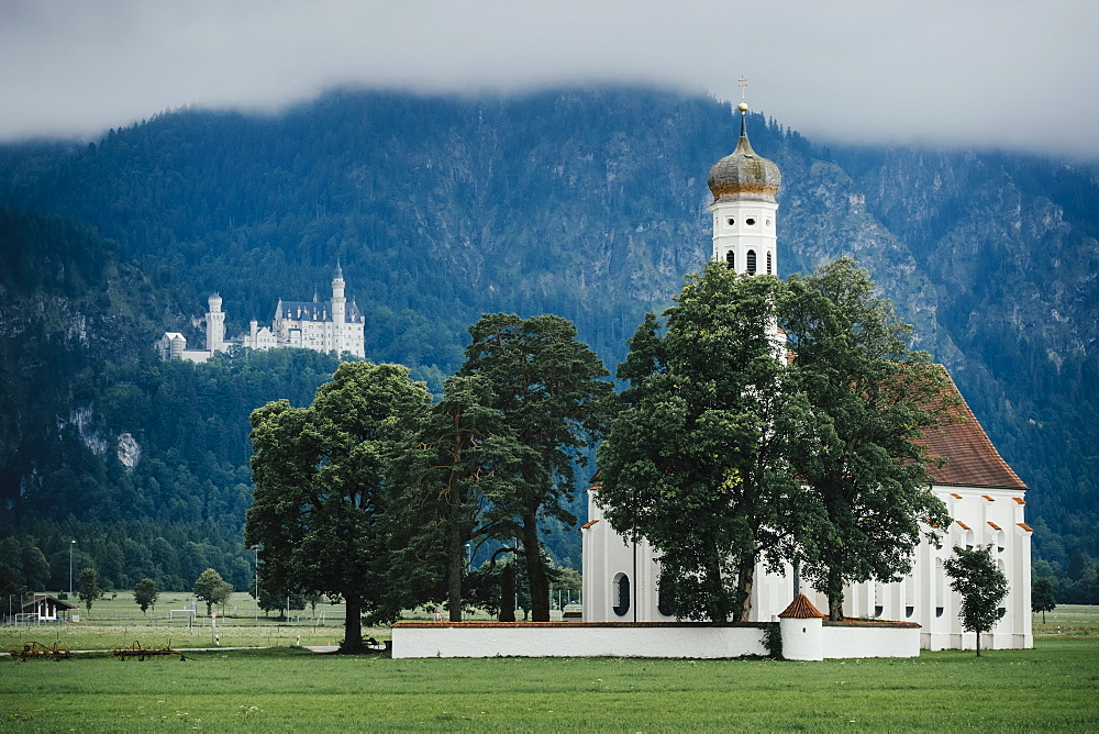 View of St. Coloman Church with Neuschwanstein Castle in background, Hohenschwangau, Bayern, Germany