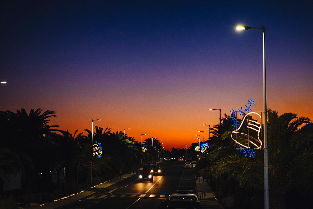 Christmas bell light decorations on street lamps over road at sunset, Costa Teguise, Lanzarote