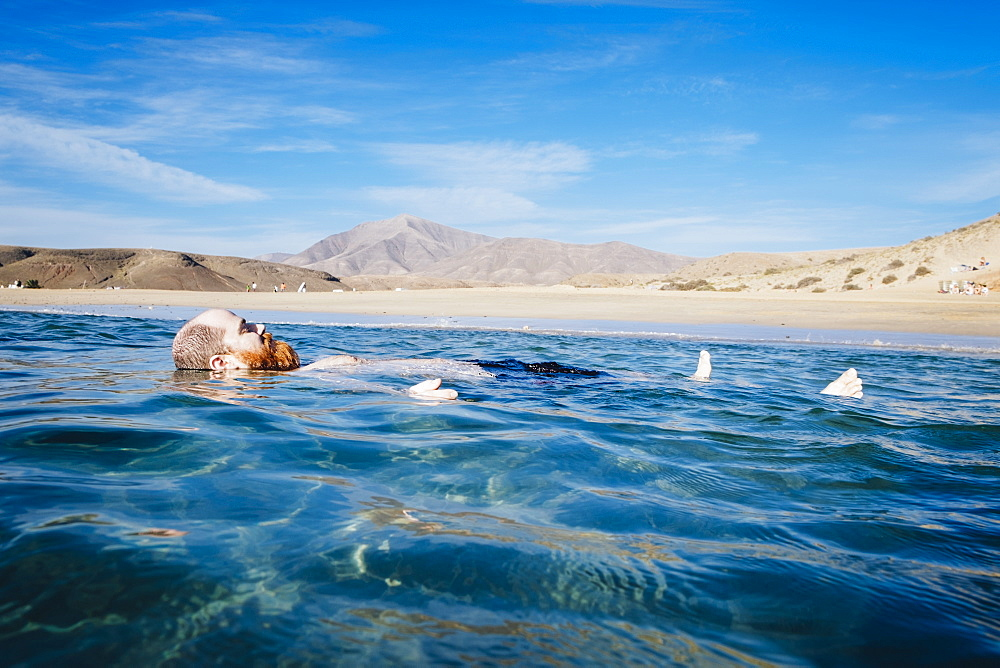 Carefree man floating in blue ocean water, Papagayo Beach, Lanzarote, Canary Islands, Spain