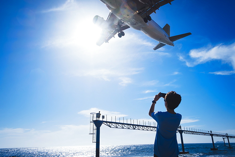 Boy with camera phone photographing airplane flying low overhead near Lanzarote Airport