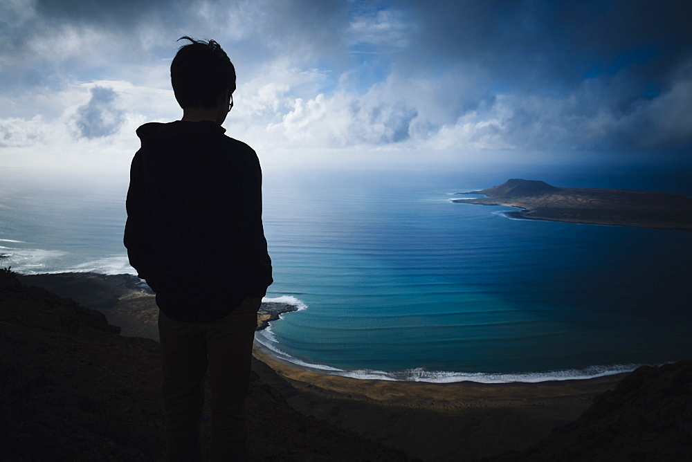 Boy looking at scenic ocean bay view with storm clouds overhead, Lanzarote, Canary Islands, Spain - 1177-2286