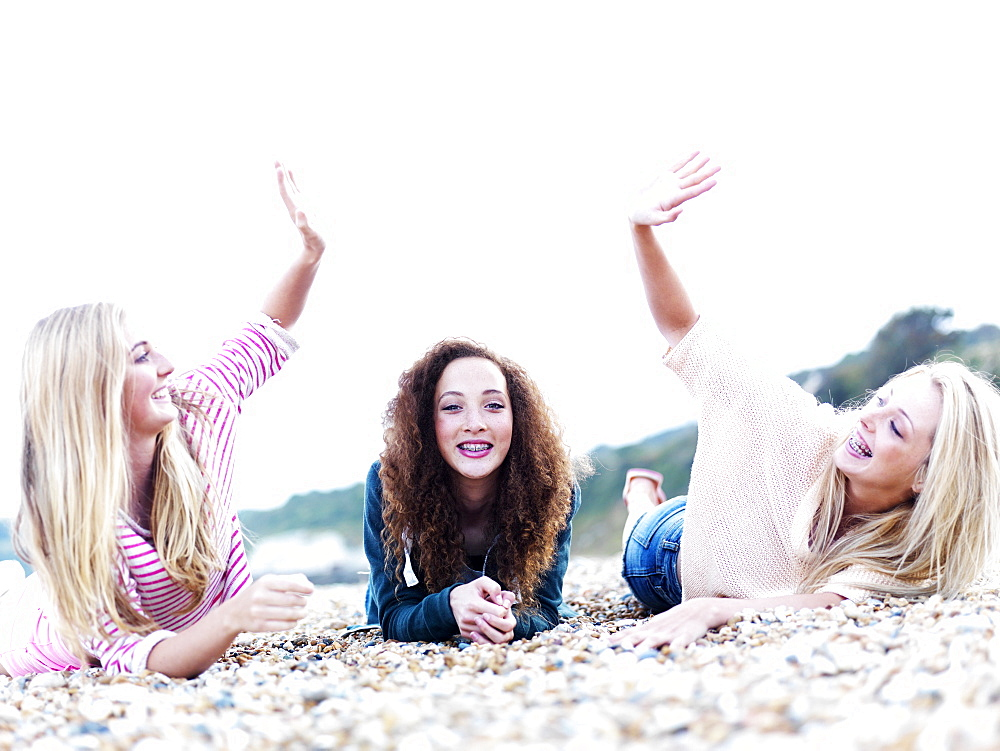 A girl lying in between two friends high-fiving above her at the beach