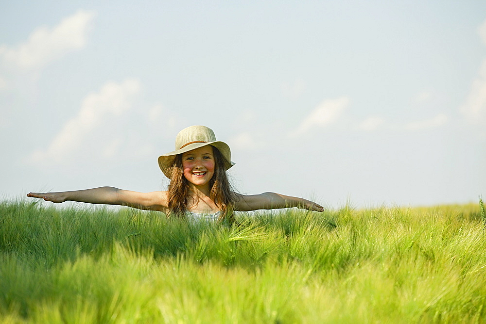 Portrait carefree girl with arms outstretched in sunny, rural green field