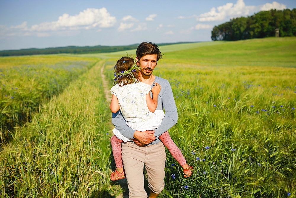 Portrait father carrying daughter in sunny, idyllic rural field