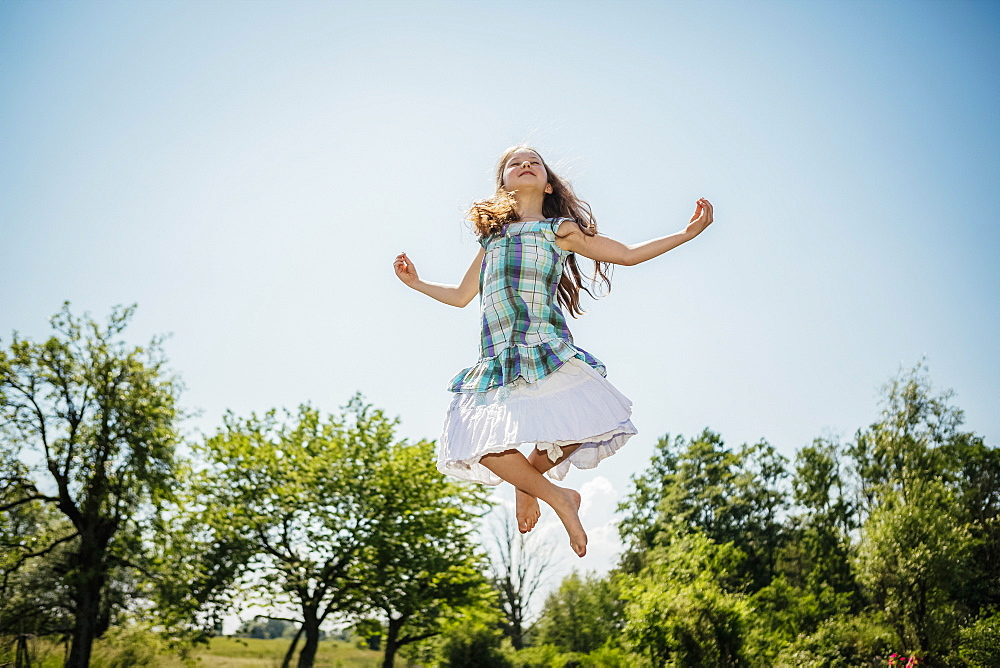 Carefree girl in dress jumping for joy in sunny backyard - 1177-2351