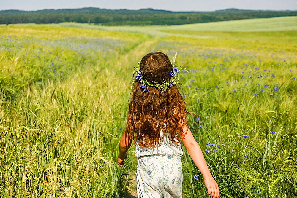 Girl with flowers in hair walking in sunny, idyllic green field