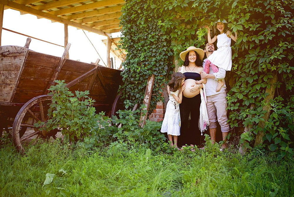 Portrait pregnant family in rural garden