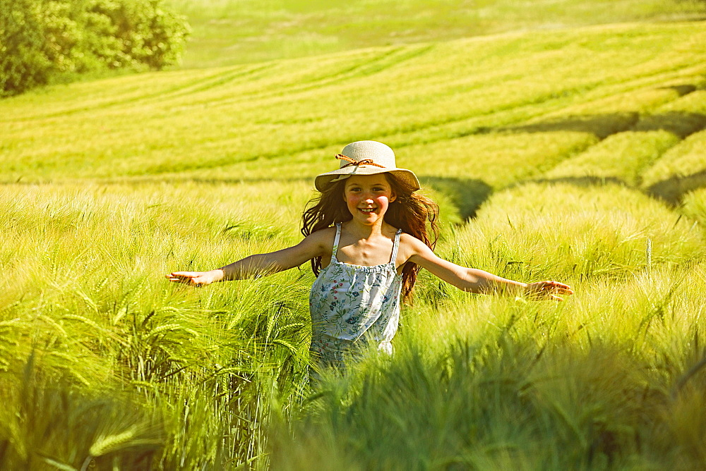 Portrait happy, carefree girl running sunny rural field