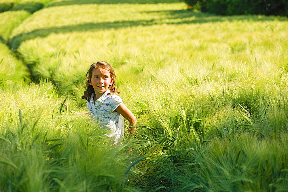 Portrait smiling girl in rural, green wheat field
