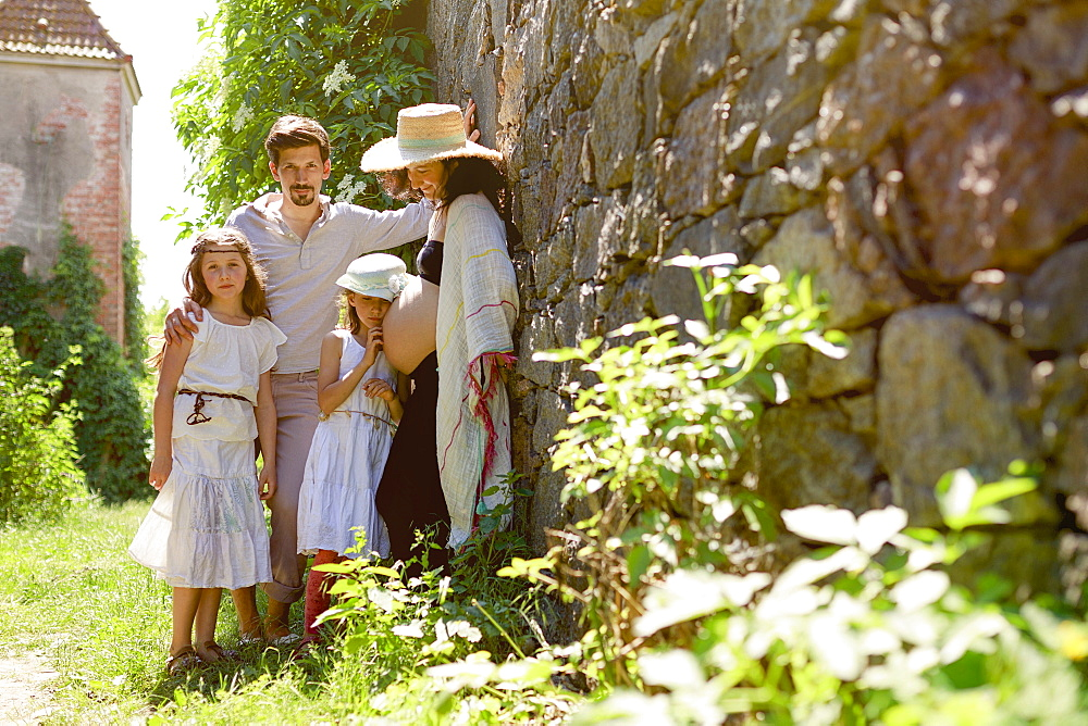 Portrait pregnant family at sunny stone wall in garden