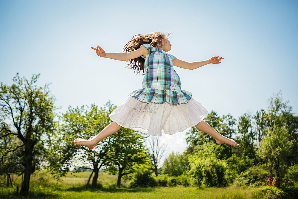 Carefree girl in dress jumping for joy in sunny backyard - 1177-2367