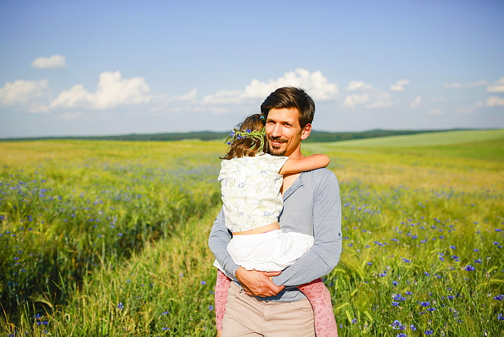 Portrait father holding daughter in sunny, idyllic rural field with wildflowers