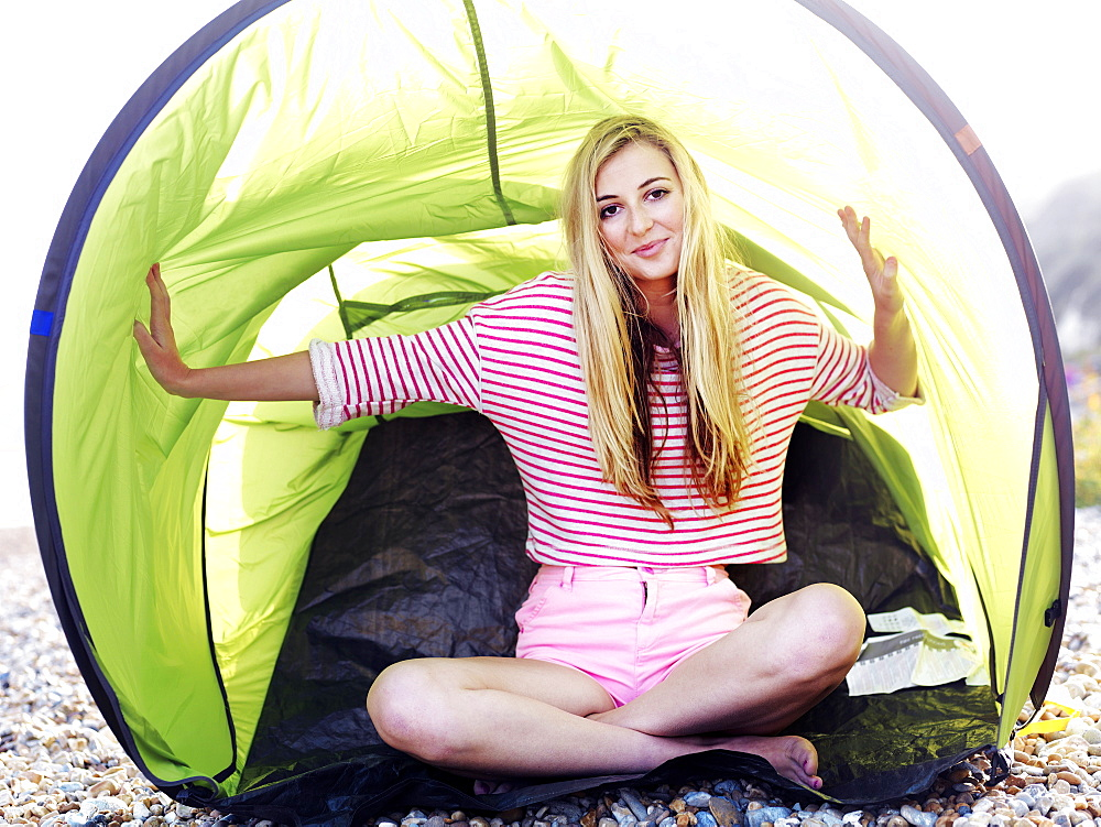 A young woman sitting in a beach tent on a rocky beach