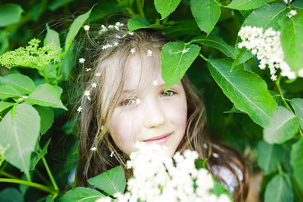 Portrait girl with flowers in hair in blooming bush