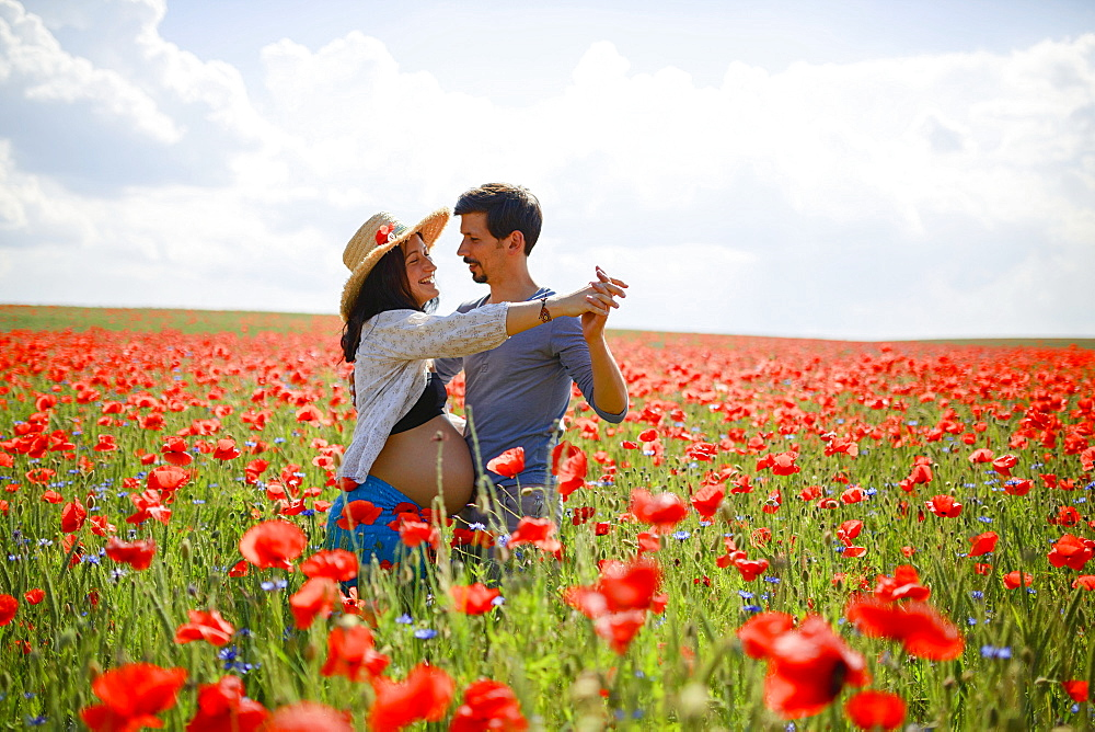 Pregnant couple dancing in sunny, idyllic rural red poppy field