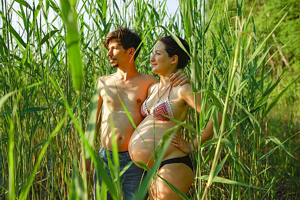 Pregnant couple in bikini and swim trunks standing in rural green corn field