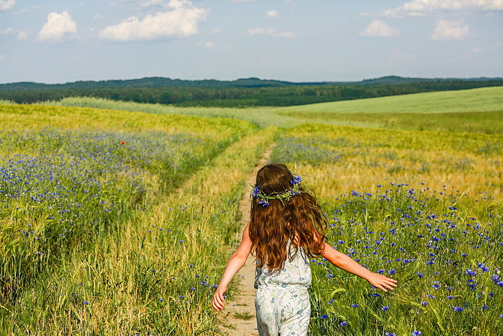 Girl running in sunny, rural idyllic green field with wildflowers