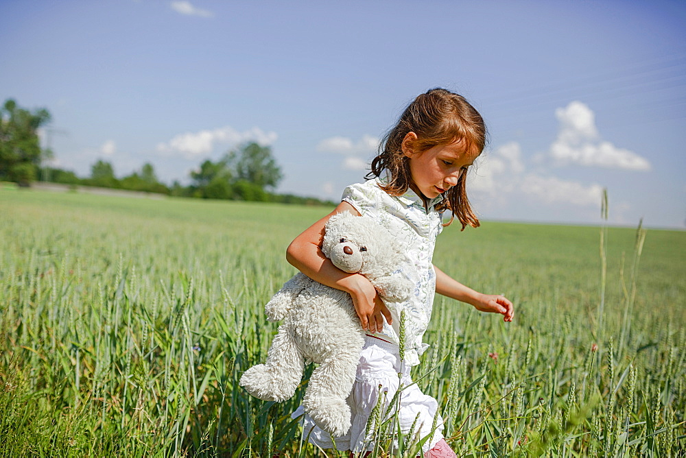 Girl with teddy bear walking in sunny, rural green field