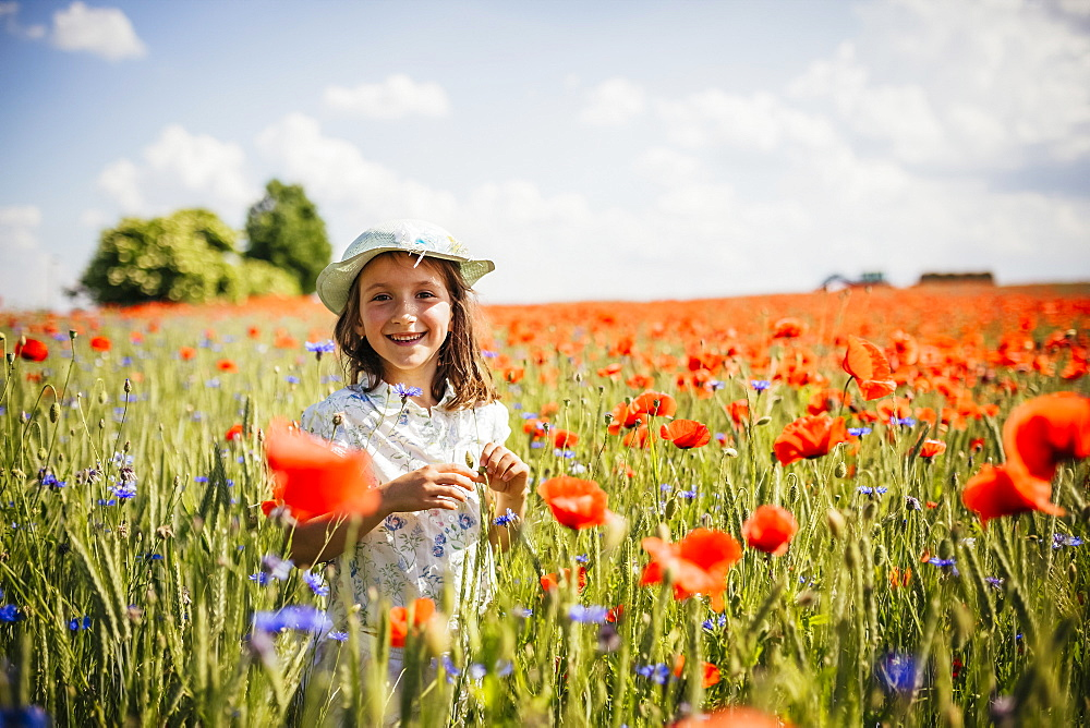 Portrait happy, carefree girl in sunny, idyllic rural red poppy field