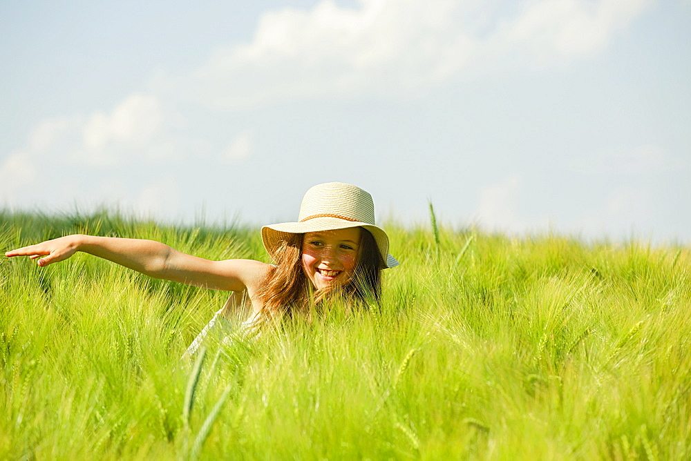 Carefree, happy girl in sunny rural green wheat field