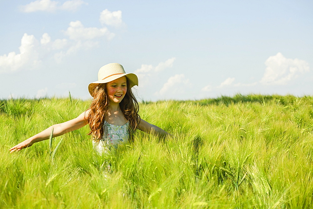 Carefree girl walking in sunny, idyllic green rural field