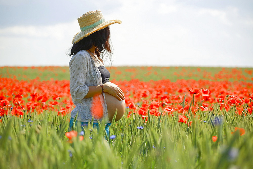 Pregnant woman standing in sunny, idyllic rural field with red poppies