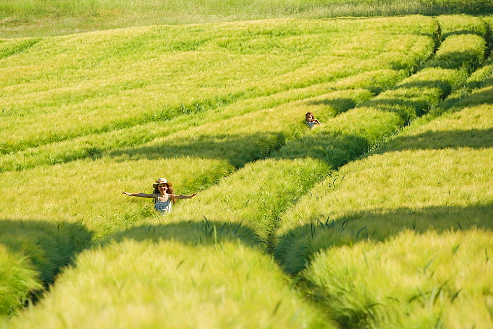 Carefree girls running in sunny, idyllic green rural wheat field