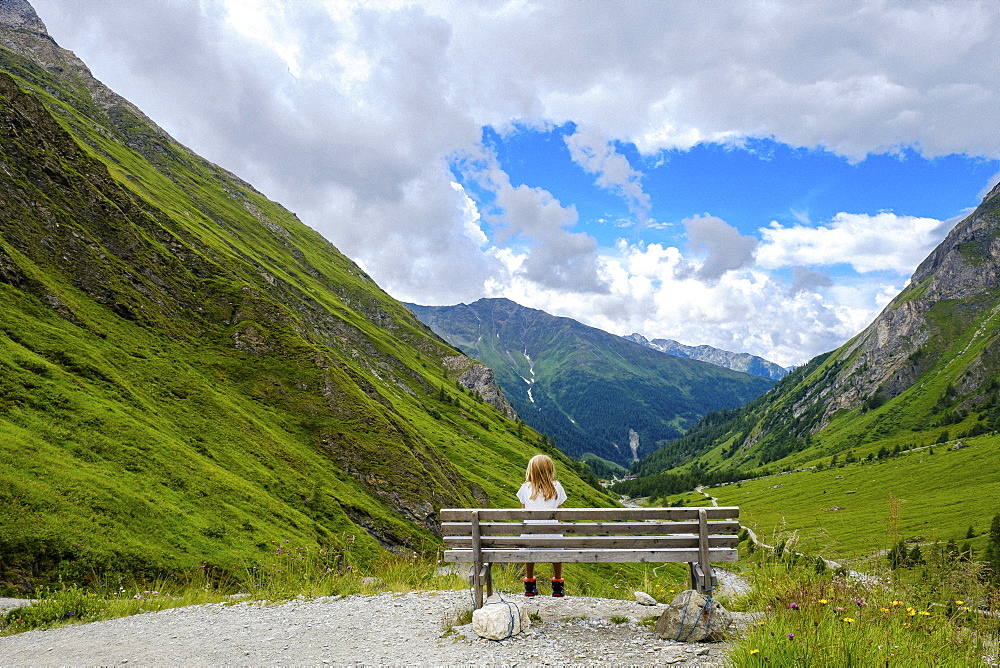 Girl sitting on bench looking at scenic mountain view, Innergschloess, Tyrol, Austria - 1177-2424