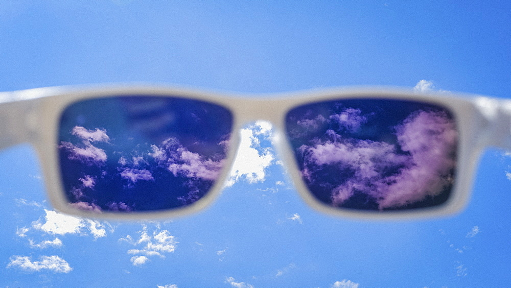 Personal perspective sunglasses looking up at sunny blue sky with clouds