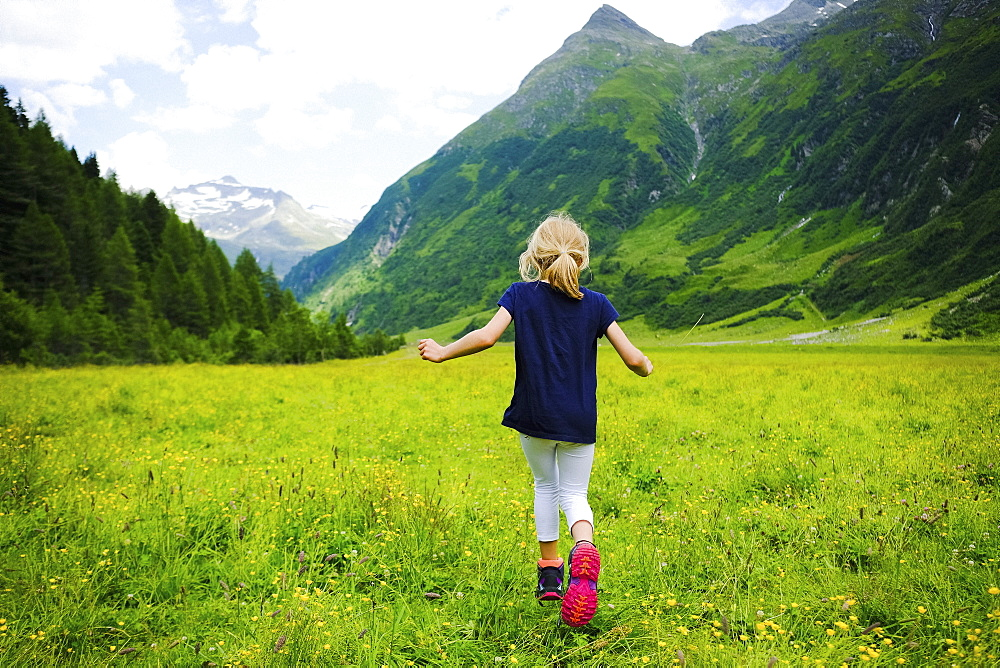 Carefree girl running in idyllic mountain valley, Innergschloess, Tyrol, Austria