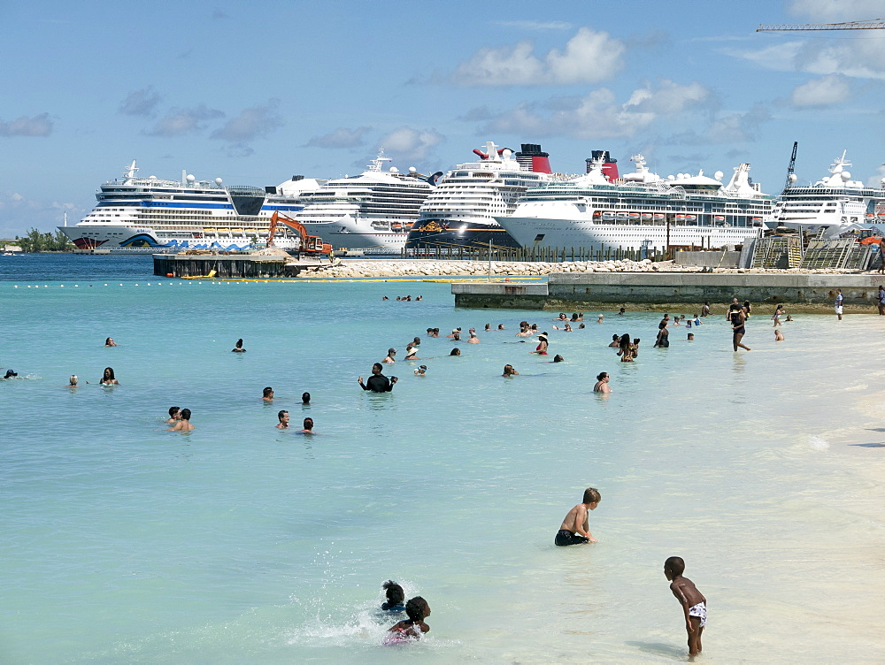 Tourists swimming in sunny ocean with cruise ships in background, Nassau, Bahamas