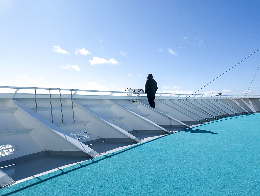 Tourist standing on sunny deck of cruise ship