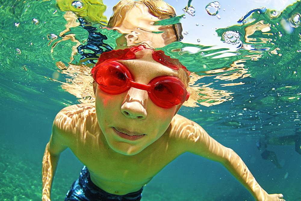 Portrait boy in swimming goggles swimming underwater